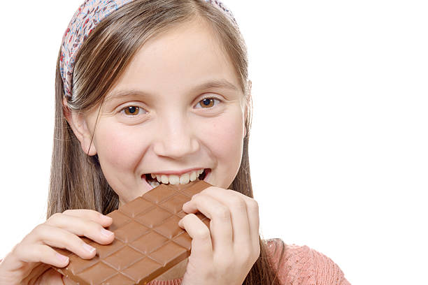 a preteen girl eats chocolate, isolated on white